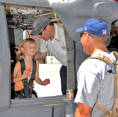 Lt Col John Bernhart, right, 58th Special Operations Wing, tours an HH-60G Pave Hawk with his daughter, Grace, with assistance from Master Sgt. Brian Sato, 512th Rescue Squadron, during the wing picnic May 13, here.  U.S. Air Force photo by Adam Wooten