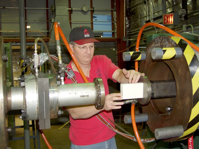 Machinist Larry Phipps at the Air Force's Arnold Engineering Development Center loads a foam projectile into an 86-foot-long rectangular barrel used to conduct impact testing for the Space Shuttle Return to Flight program.