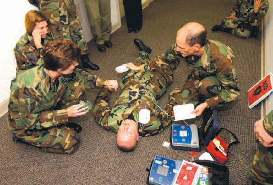 With Staff Sgt. Isaac Wilson acting as a heart attack victim in Bldg. 460, Tech Sgt. Mickey Leckie, right, and Master Sgt. Beverly Justice go through rescue procedures using the Automatic External Defibrillator during a recent training session.