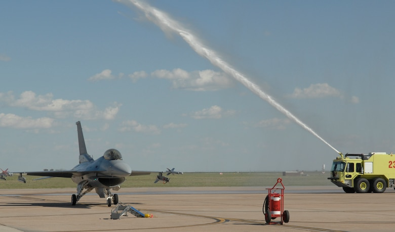 CANNON AIR FORCE BASE, N.M. -- A firetruck hoses down an F-16 piloted by Lt. Col. Brad Kearney, 523rd Fighter Squadron commander, on May 10 following the final flight of the squadron. The squadron inactivated on May 23. (U.S. Air Force photo by Airman Erik Cardenas)