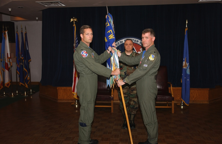 CANNON AIR FORCE BASE, N.M. -- Col. Jeff McDaniels, 27th Operations Group commander, receives the guidon from Lt. Col. Brad Kearney, 523rd Fighter Squadron commander, shortly before the squadron's  inactivation in a ceremony on May 23. (U.S. Air Force photo by Tech. Sgt. Scott Mackay)