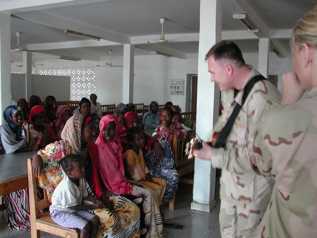 Master Sgt Jimmy Weber and Staff Sgt Lara Murdzia from the Heartland of America Band use music to make new friends at an orphanage in Jubuti, Africa on their recent deployment