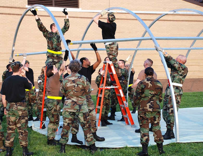 The Medical Group works together to build portable structure called an Alaskan shelter during Medical Unit Readiness Training at the clinic May 18. An Alaskan structure serves as a hospital in a deployed environment. (Photo by Airman 1st Class Jessica Lockoski)
