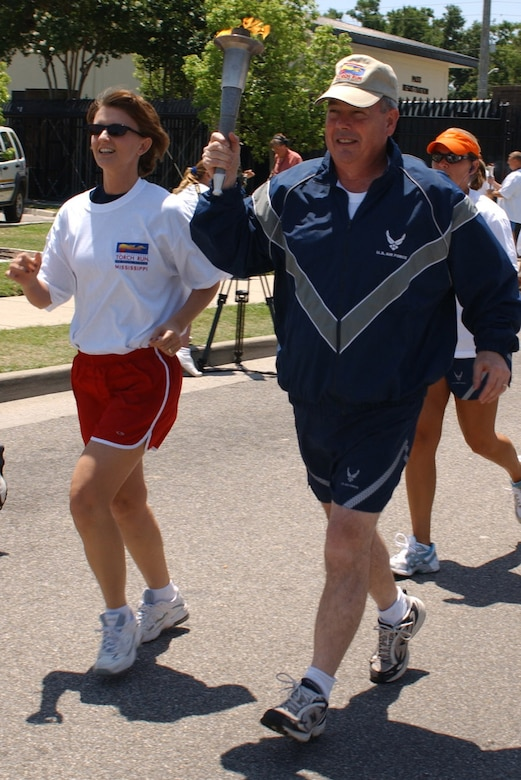 Paul Capasso, 81st Training Wing commander, with wife Laura alongside, accepted the torch from 81st Security Forces Squadron members at the White Avenue Gate Friday.  The 81st SFS members, along with Biloxi police, ran the torch to Keesler's gate as part of the Special Olympics Law Enforcement Torch Run.   (U. S. Air Force Photo by Kemberly Groue)