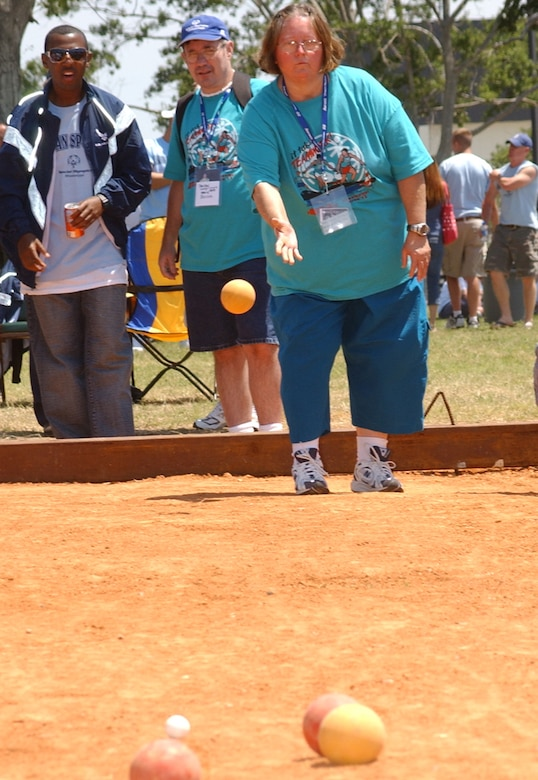 Donna Tillman, Area 12, throws a bocce ball Saturday at the Triangle Track as an Airman sponsor looks on.  Each athlete was assigned two Airman sponsors to bunk with and escort them throughout the weekend. (U. S. Air Force Photo by Kemberly Groue)
