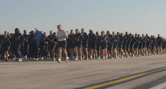 SPANGDAHLEM AIR BASE, GERMANY -- Chief Master Sgt. Vance Clarke, 52nd Fighter Wing command chief, runs alongside Airmen from the 52nd Communications Squadron during the wing fun run on the Spangdahlem Air Base flight line May 1. (US Air Force photo/Senior Airman Josie Kemp)