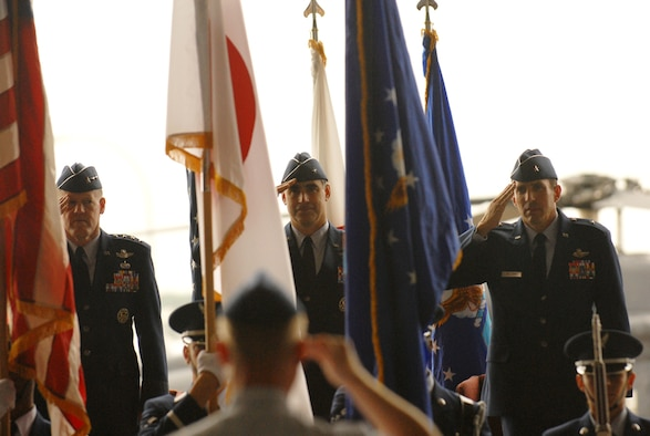 Col. Jeffrey Kennedy (foreground), 18 Wing vice commander, salutes the colors at the beginning of the change of command ceremony May 24 at Kadena AB, Okinawa. Lt. Gen. Bruce Wright, U.S. Forces Japan commander; Brig. Gen. Punch Moulton and Brig. Gen. Brett Williams are in the background. General Moulton relinquished command of the 18th Wing to General Williams during the ceremony. 