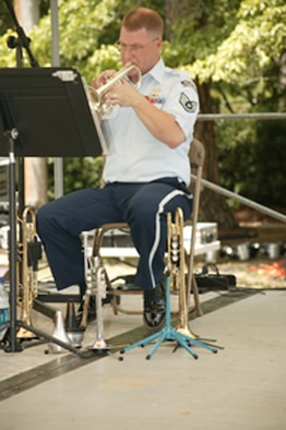 Sumter, S.C. -- Staff Sgt. Mark Nixon, U.S. Air Force Heritage of America Brass Quintet band member plays the trumpet at the Iris Festival May 25. The festival has been ranked among the top twenty festivals in the Southeast. This year marks sixty-seven years of the event and it draws thousands of people into the city of Sumter. Comprised of two trumpets, horn, trombone, and tuba, the quintet is part of the U.S. Air Force Heritage of America Band, a 60-member ensemble based at Langley Air Force Base, Va. The band played throughout the weekend and at the Sumter County Veterans Association Memorial Day Program on May 28.  (U.S. Air Force photo by Kimberly Champagne)