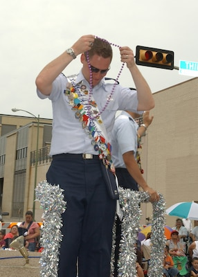 Lackland Ambassador Capt. Brent Dishman, riding the joint military float in the Battle of Flowers Parade on April 27, dons a string of Fiesta beads handed to him by aparade spectator at Broadway and Third Street. Fiesta is an annual 10-day event with more than 100 scheduled events designed to honor the heroes of the Alamoand the Battle of San Jacinto. Lackland AFB, Texas, is represented in numerousevents during the celebration, including the opening ceremonies, the Texas Cavaliers River Parade, the Battle of Flowers Parade, the Fiesta Flambeau night parade, Fiesta in Blue, the Air Force at the Alamo and the Fiesta Military Paradeon base. (USAF photo by Alan Boedeker)