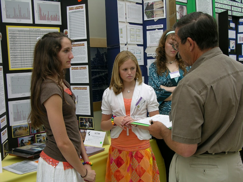 LOS ANGELES -- Kaitlyn Wright (left) and Lindsey Lewis (center), Desert High School seniors, explain their project to one of the judges during the California State Science Fair at the California Science Center in Los Angeles on May 22. Ms. Lewis and Ms. Wright received first place for their plant biology project. Kehly Kirk, another DHS student, placed third, also for plant biology. Robert Thurman and Keith Hines, both DHS seniors, also received a special award for doing a low-cost and hands-on project. (Photo by Dawn Waldman)