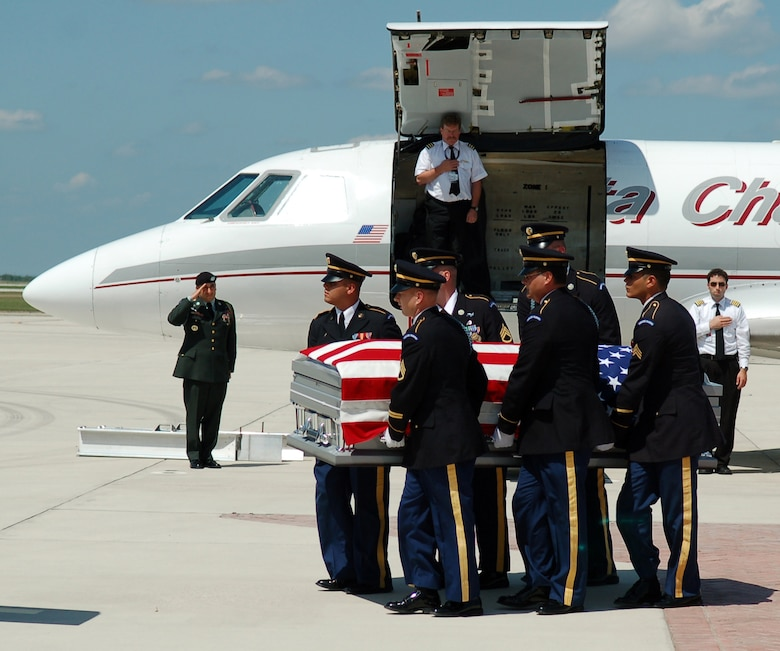 LAUGHLIN AIR FORCE BASE, Texas -- Honor Guard members from Fort Sam Houston carries the American Flag draped casket of U.S. Army Pvt. Oscar Sauceda Jr., 21. With a group of his family close by, a small charter plane carrying his body touched down at Laughlin May 29, to bring him home town of Del Rio, Texas. (U.S. Air Force photo by Staff Sgt. Austin May)