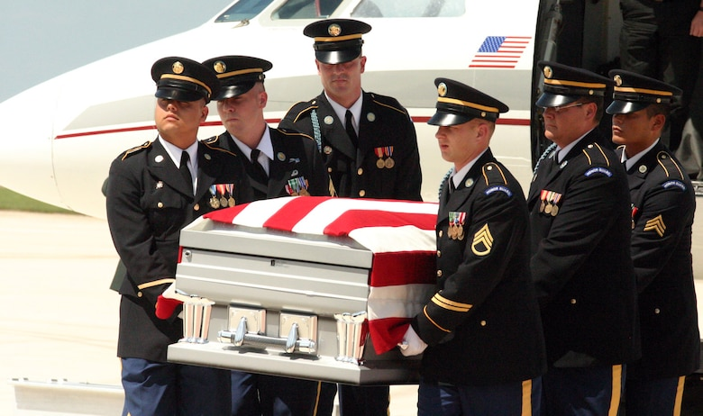 LAUGHLIN AIR FORCE BASE, Texas -- Honor Guard members from Fort Sam Houston carries the American Flag draped casket of U.S. Army Pvt. Oscar Sauceda Jr., 21. With a group of his family close by, a small charter plane carrying his body touched down at Laughlin May 29, to bring him home town of Del Rio, Texas.(U.S. Air Force photo by Airman Sara Csurilla)