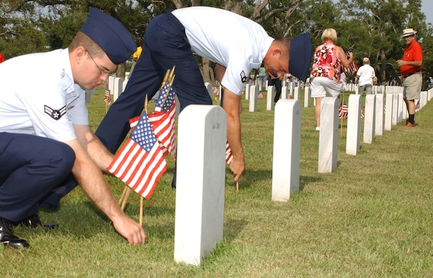 From left, Airmen 1st Class Marvin Howdershell and Nicholas Small place flags in front of head stones in Biloxi National Cemetery Saturday in preparation for the Memorial Day observance held on the grounds Monday.  The Airmen are technical training students in the 335th Training Squadron.  (U. S. Air Force photo by Kemberly Groue)