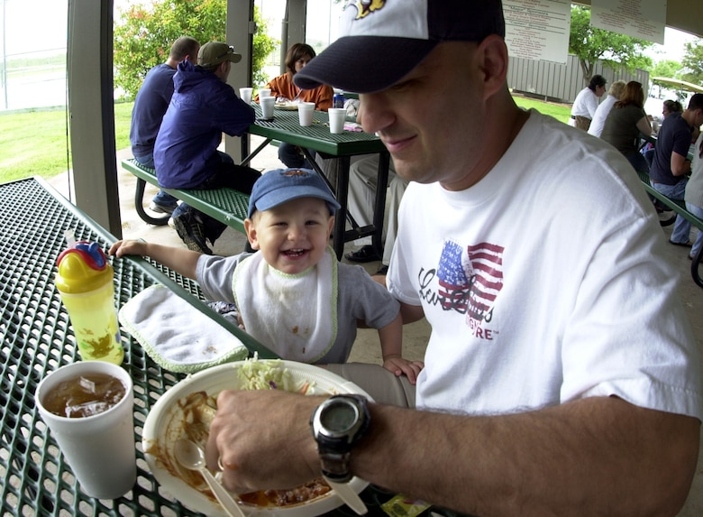 "Eighteen-month-old James ""Jimbo"" Nemec smiles for the camera while his father, Master Sgt. James Nemec, 17th Mission Support Squadron first sergeant, scoops up some pinto beans from his plate during the Goodfellow Appreciation Day Picnic May 19 at Goodfellow Recreation Camp at Lake Nasworthy. (U.S. Air Force photo by Airman 1st Class Luis Loza Gutierrez)"