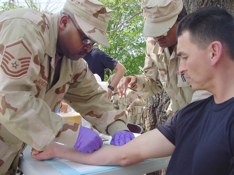 Master Sgt. Lesley Anderson pulls a needle out of a catheter tube after drawing blood from a vein in Capt. Joe Whittington's arm during transition team training at Fort Riley, Kan. Sergeant Anderson is attending the 60-day, pre-deployment training from McConnell Air Force Base, and Captain Whittington is attending from Maxwell Air Force Base, Ala. (Photo by Army Master Sgt. Jack Lee)
