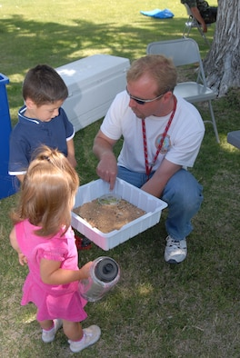 Wesley King (right), Environmental Management staff, shows a small desert tortoise to Zachary Clark (left), 3, and his sister Sophea (foreground), 1, during the 101 Critical Days of Summer Campaign Kickoff at the Oasis Community Center on May 24. (Photo by Airman 1st Class Julius Delos Reyes)