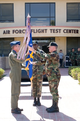 Maj. Gen. Curtis Bedke (left), Air Force Flight Test Center commander, hands over the 95th Air Base Wing flag to Col. Bryan Gallagher (right), former 95th ABW vice-commander, during an assumption of command ceremony at building 1 here May 29. With the ceremony, Colonel Gallagher officially took command of the 95th ABW. (Photo by Mike Cassidy)