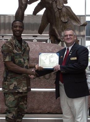 DAYTON, Ohio -- Christian Cross (right), a volunteer at the National Museum of the United States Air Force, accepts the Team Wright-Patt Volunteer of the Quarter award from 88th Air Base Wing Vice Commander Col. Neal B. McElhannon. (U.S. Air Force photo)