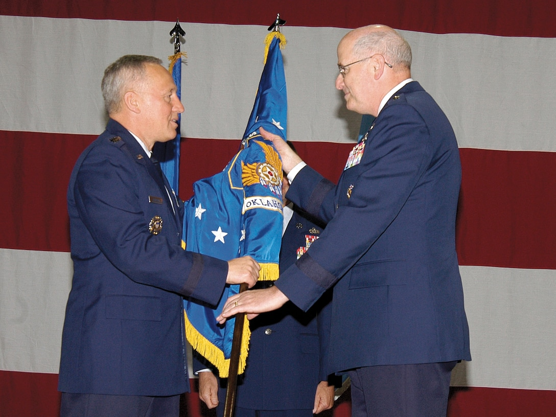 Gen. Bruce Carlson, left, passes command of the Oklahoma City Air Logistics Center to Maj. Gen. Loren M. Reno May 30.  The commander of Air Force Materiel Command passed the guidon in a traditional ceremony before approximately 1500 workers, civic and military leaders and retired Tinker commanders gathered in a Bldg. 3001 aircraft dock. (Air Force photo by Margo Wright)