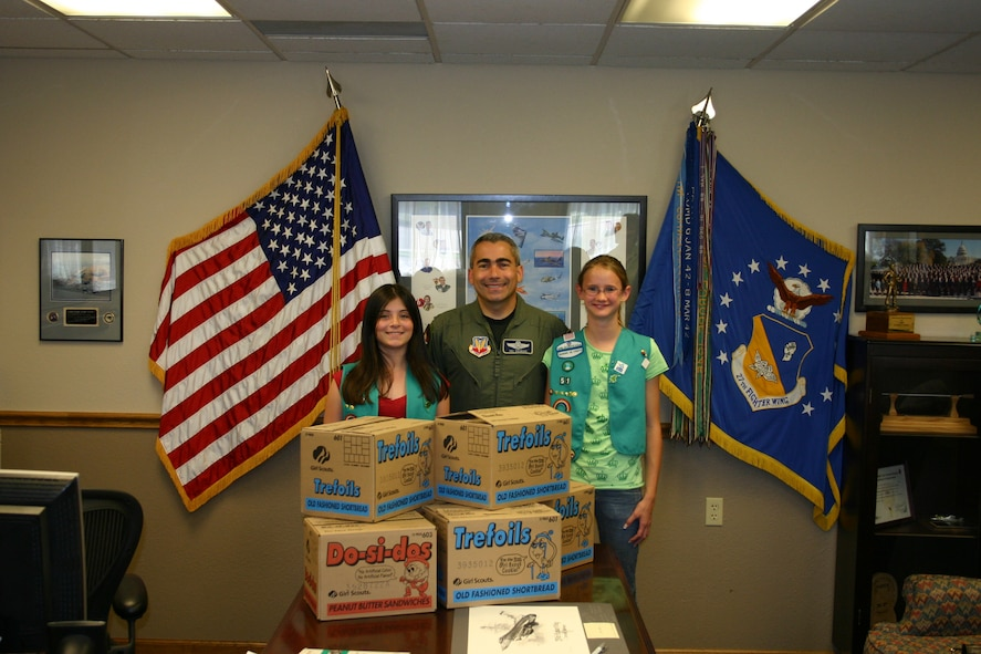 CANNON AIR FORCE BASE, N.M --Girl Scouts Angelina Garcia (left) and Rebecca Dewbre (right), from Girl Scout Troop 51, stand beside Colonel Valentino Bagnani III, 27th Fighter Wing vice commander, with boxes of Girl Scout cookies that will be sent to servicemembers serving in Afghanistan and Iraq. (U.S. Air Force photo by Airman Elliott Sprehe)