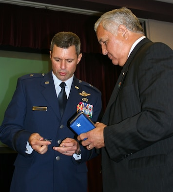 Brig. Gen. Greg Biscone, 509th Bomb Wing commander, presents a commander's coin to Congressman Silvestre Reyes, who represents the 16th District of Texas in the U.S. House of Representatives, at the base community council luncheon at Mission's End May 29. As a senior member of both the Armed Services and Select Intelligence Committees, Congressman Reyes is a key member of Congress on defense and military issues.  He attended the luncheon with Missouri Congressman Ike Skelton, and U.S. Navy Rear Admiral Mark Ferguson, Navy legislative affairs chief. Congressman Reyes, who served in the U.S. Army and is a Vietnam War veteran, thanked Whiteman members for their service and patriotism. (U.S. Air Force photo/Staff Sgt. Rob Hazelett)