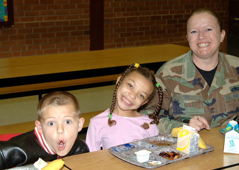 MCCONNELL AIR FORCE BASE, Kan. -- Technical Sergeant Wendi Fox, 22nd Aircraft Maintenance Squadron, poses with two children from the Wineteer Elementary School during their lunch break for the Lunch Buddies program Oct. 25. The Lunch Buddies program is a nationwide program that pairs a caring adult with an elementary students consisting of 1st and 2nd graders, McConnell Air Force Base personnel volunteer to participate in this program every Thursday.  (Photo by Airman 1st Class Justin Shelton)