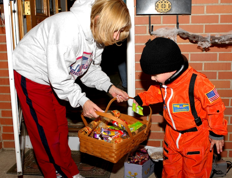 MINOT AIR FORCE BASE, N.D. -- Austin Pritchett, 3, son of Capt. Michael Pritchett, 5th Operation Support Squadron, picks out some goodies from Maureen Bell's trick-or-treat basket. Mrs. Bell is the wife of Col. Greg Bell, 5th Bomb Wing vice commander. Kids all over Minot Air Force Base celebrated Halloween by trick-or-treating Oct. 31. (U.S. Air Force photo by Airman 1st Class Sharida Bishop)
