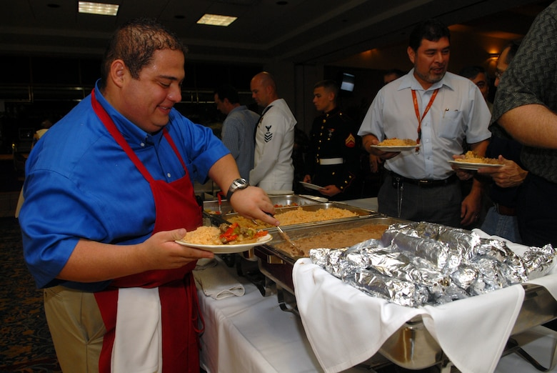 Simon Rincon, owner of Nachos Restaurant, serves up a plate of Mexican food for guests attending the observance luncheon Oct. 11 at the Event Center. (U.S. Air Force photo by Airman 1st Class Kamaile Chan)