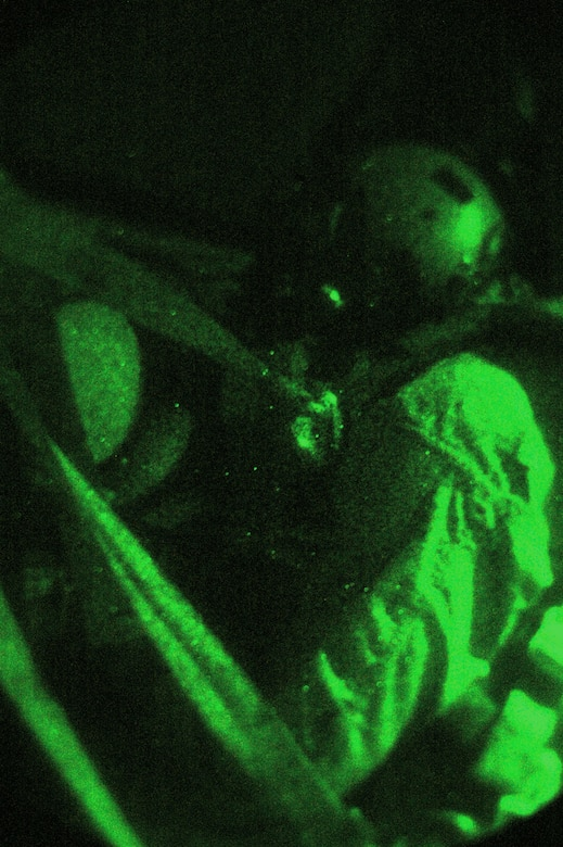SOUTHWEST ASIA - Tech. Sgt. Kevin Letz, 40th Expeditionary Airlift Squadron loadmaster, watches through a C-130 window during a leaflet drop mission. Sergeant Letz watches for enemy activity using night vision to assist ensuring the safety of the crew and aircraft from possible enemy attack. Sergeant Letz is deployed from Dyess Air Force Base, Texas. (U.S. Air Force photo/Staff Sgt. Jason Barebo