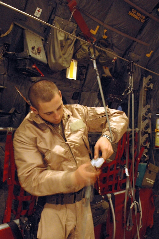 SOUTHWEST ASIA - Senior Airman William Moody, 40th Expeditionary Airlift Squadron loadmaster, sets up static lines to help rip open boxes of leaflets. (U.S. Air Force photo/Staff Sgt. Jason Barebo)