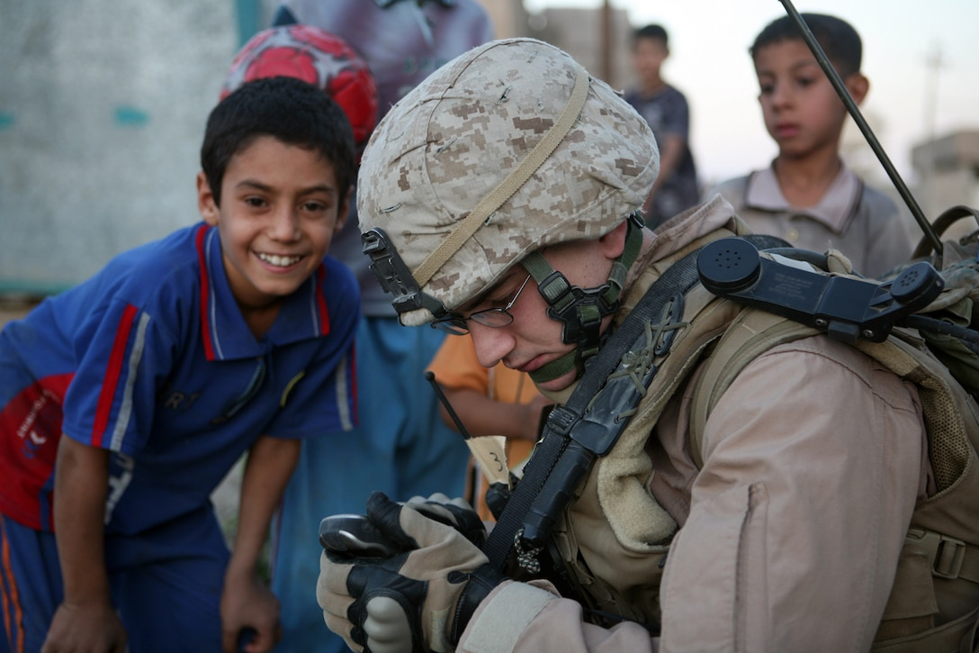 """Cpl. Jordan M. Moehnle, 21, of Los Angeles, takes time out of leading his squad in a patrol through Fallujah's Nazaal district to spend some time interacting with local children. Moehnle, who is on his second tour in Iraq, said the changes he has witnessed since he was last here in 2006 have been dramatic. """"The city was like the Wild West, we'd put our heads and and drive down (the middle of Fallujah) and hope not to get shot,"""" he said. """"Since we've been here (this year), we can stop and shoot the breeze."""""""