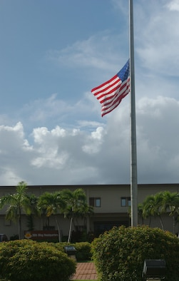 The base flag in front of 36th Wing Headquarters is lowered Nov. 1 to mark the passing of Retired Brig. Gen. Paul Tibbets. General Tibbets was the pilot of The Enola Gay, which dropped the first atomic weapons employed in combat. General Tibbets' mission helped bring about a quick end to World War II, which saved countless American lives by avoiding an invasion of the Japanese home islands. Most historians agree if such an invasion had taken place, the heavily fortified Japanese cities and military installations would've exacted a horrific price in terms of allied and American losses. (Air Force photo/Senior Airman Brian Kimball)