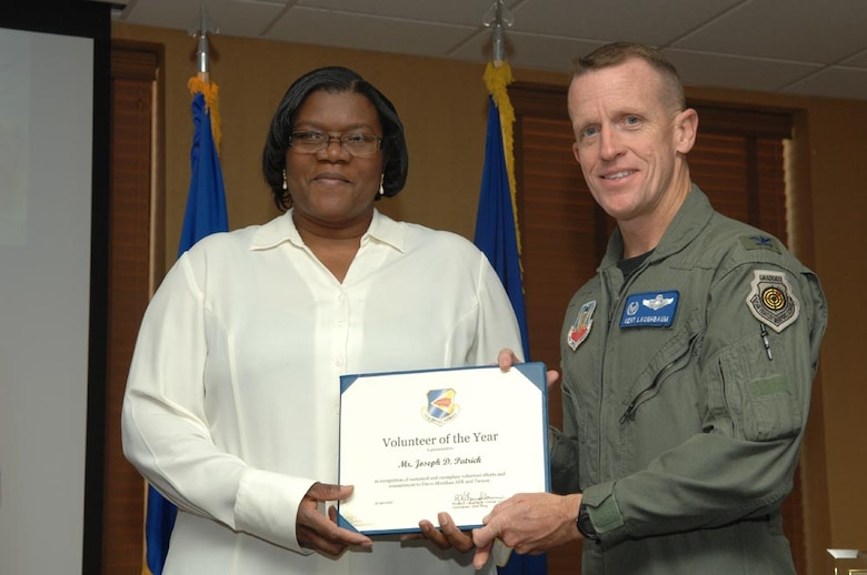 Mr. Joseph Patrick's wife accepts his award from Col. Kent Laughbaum, 355th Fighter Wing commander. (Courtesy photo)