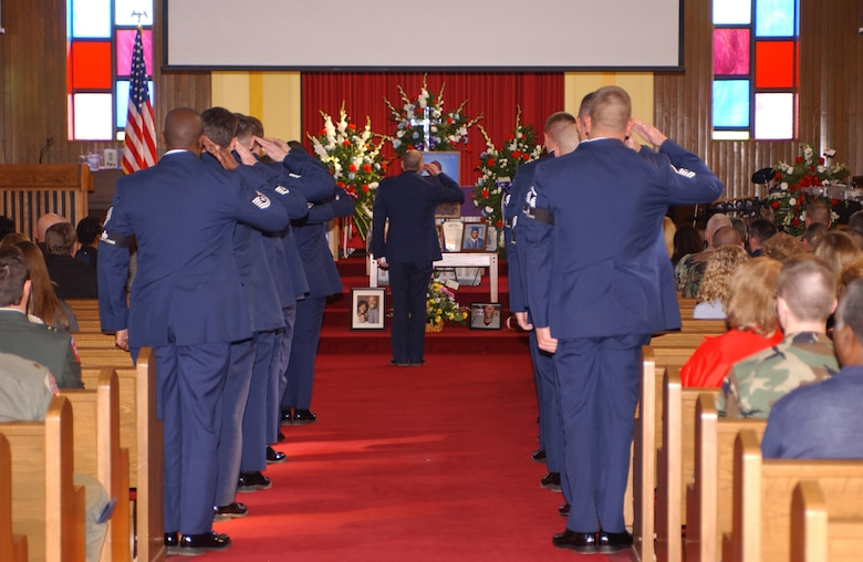 """CANNON AIR FORCE BASE, N.M. -- Members of the 27th Civil Engineer Squadron's explosive ordnance disposal flight salute during the final roll call honoring U.S. Air Force Capt. Kermit Evans, Sr. during a memorial ceremony Dec. 15, 2006.  Evans was killed in action Dec. 3, 2006, while serving in Iraq.   Airman 1st Class Randi Flaugh describes this moment as, """"A way to commemorate a son, husband, brother, father, and most importantly, a military hero."""" (U.S. Air Force photo by Airman 1st Class Randi Flaugh)"""