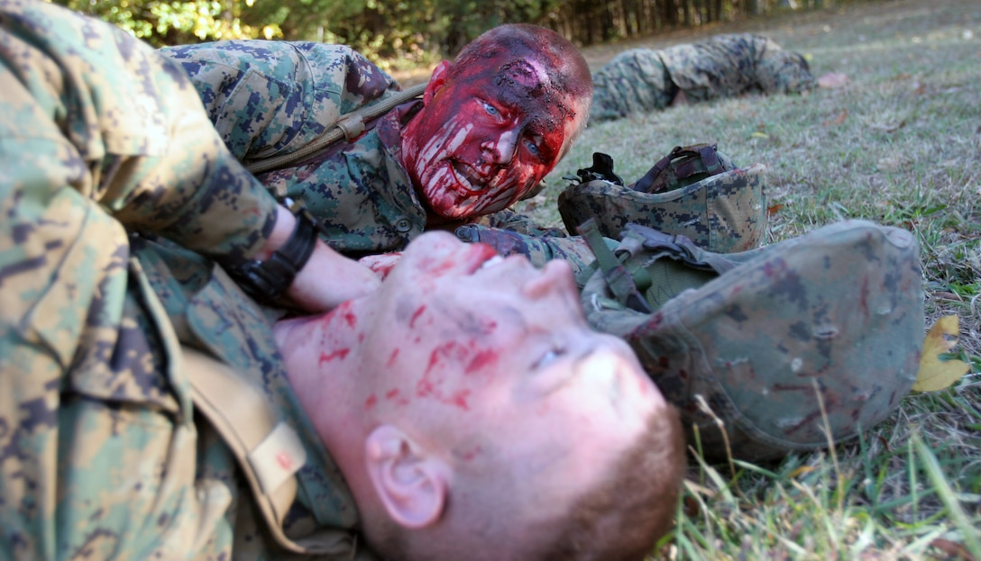 An injured Marine checks another for signs of life. Marines and Sailors from the 24th Marine Expeditionary Unit, Combat Logistic Battalion 24, practiced treating and evacuating patients during the massive casualty scenario here. The exercise is part of the MEU's Realistic Urban Training, focused on provided the sights and sounds of an actual battlefield to the Marines.