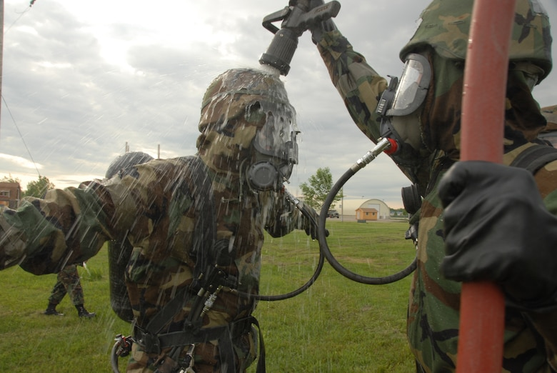 Staff Sgt. Matthew Lasek decontaminates Airman 1st Class Lyndsey Barclay, both of the 138th Civil Engineer Squadron, after completing the dike, dam, divert and retain practical portion of the HAZMAT operations level certification course at the North Dakota Air National Guard Readiness Training Site June 6. (U.S. Air Force photo by Senior Master Sgt. David H. Lipp)