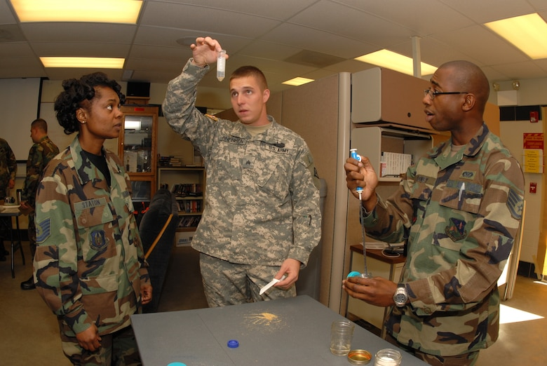 Instructor Sgt. Justin C. Rinearson,  61st CST, center, demonstrates the amount, substance and procedure for testing various chemical and toxic agents to Tech. Sgt. Angela Staton, 436th Civil Engineer Squadron, left, and Staff Sgt. Kimani Cadney, 159th Fighter Wing, during an emergency management training course at the North Dakota Air National Guard Regional Training Site, Fargo, N.D., Sept. 12. (U.S. Air Force photo by Senior Master Sgt. David H. Lipp)