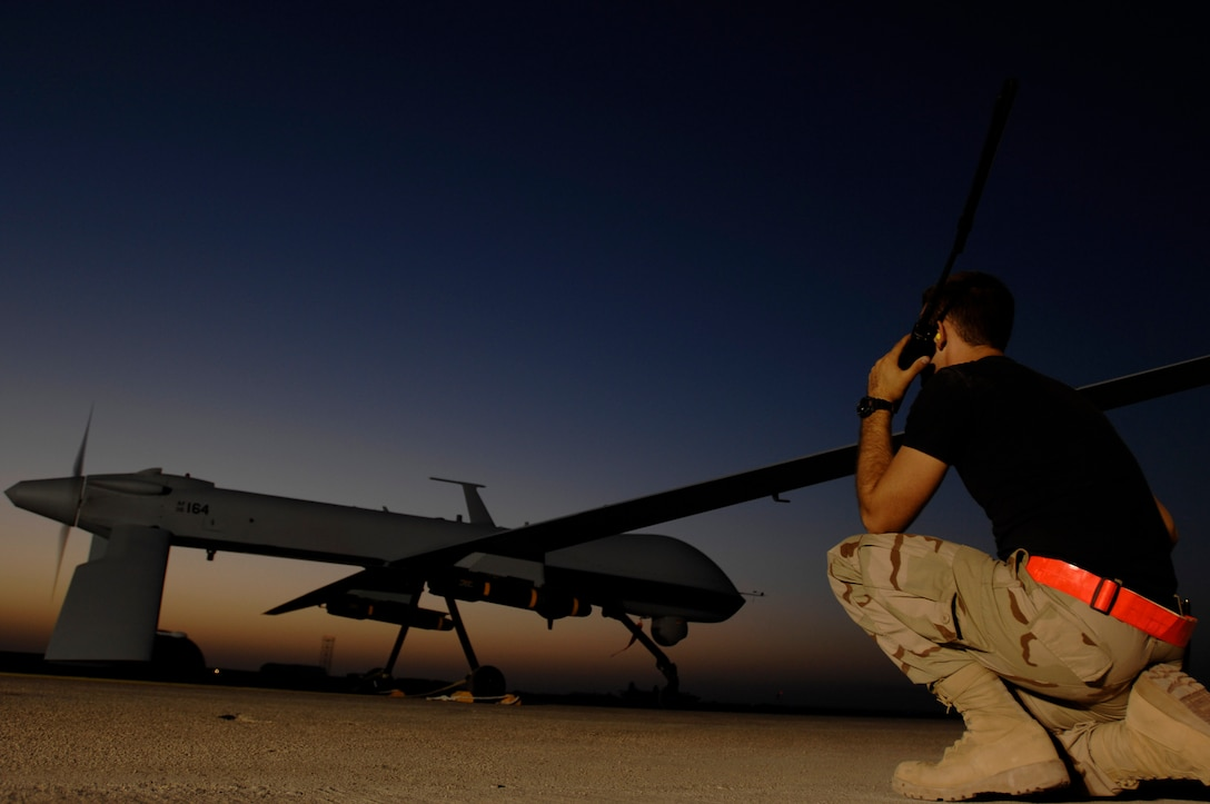 Airman 1st Class Justin Cole communicates with the pilot of an MQ-1 Predator Unmanned Aerial Vehicle in preparation for a night mission Nov. 5 at Ali Base, Iraq. The Predators are now fully operational and have begun 24-hour operations. Airman Cole is deployed from Creech Air Force Base, Nev. (U.S. Air Force photo/Airman 1st Class Jonathan Snyder)