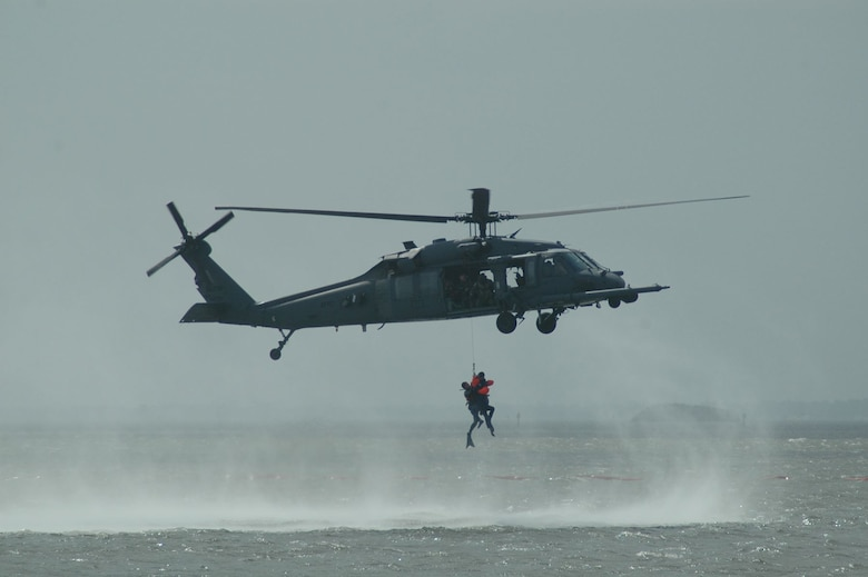 "Para-rescuemen from the 920th Rescue Wing, retrieve a ""downed"" pilot from the Banana River during a mock-rescue exercise during the World Space Expo. The rescue was performed with the use of a specially equipped HH-60 Pavehawk search and rescue helicopter. (USAF photo by Maj. Greg Harland)"