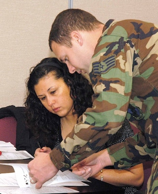 Staff Sgt. Jason Wilkins, 72nd Medical Group, Force Health Management, guides Capt. Lena Kuharske through forms during a Nov. 1 Reintegration Class at the Family Support Center. Capt. Kuharske, with the 72nd Mission Support Squadron, just returned from a six-month deployment in Iraq. (Air Force photo by Margo Wright)