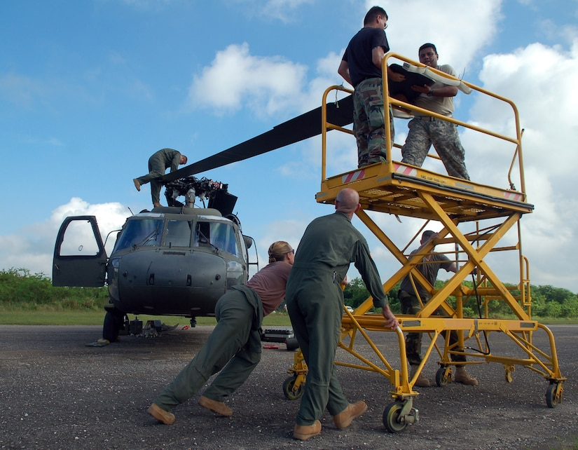 SAN ISIDRO AIR BASE, Dominican Republic -- A team of Soldiers and Airmen unfold the blades of an Army UH-60 Black Hawk helicopter in preparation for medical relief missions.  American servicemembers deployed from Joint Task Force-Bravo at Soto Cano Air Base, Honduras, to assist the Dominican Republic after it was ravaged by Tropical Storm Noel.  (U.S. Air Force photo by Staff Sgt. Austin M. May)