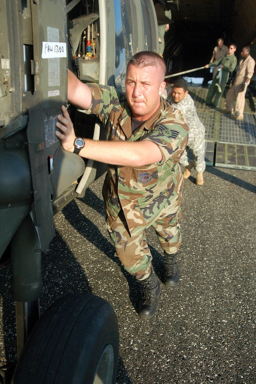 SAN ISIDRO AIR BASE, Dominican Republic -- Air Force Staff Sgt David Pagani, Joint Task Force-Bravo Medical Element, helps push an Army UH-60 Black Hawk helicopter out of an Air Force C-5 galaxy on the flight line here in preparation for medical relief missions.  American servicemembers deployed from Joint Task Force-Bravo at Soto Cano Air Base, Honduras, to assist the Dominican Republic after it was ravaged by Tropical Storm Noel.  (U.S. Air Force photo by Staff Sgt. Austin M. May)