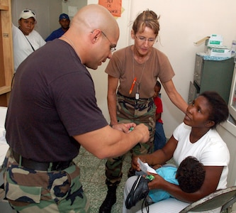 PAYA, Dominican Republic -- Air Force Staff Sgt. Luis Santa and Maj. Donnell Nicks explain medications to a Dominican mother Nov. 10 in the pediatric section of a clinic set up by U.S. servicemembers from Joint Task Force-Bravo.  The pair are part of an Expeditionary Medical Liaison Team deployed to the Dominican Republic to provide medical assistance to the island nation.  (U.S. Air Force photo by Staff Sgt. Austin M. May)