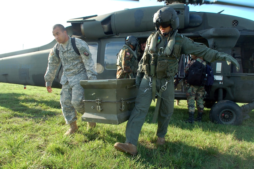 Dominican Republic -- Army Sgt. Warren Cassens and Spc. James Bilton carry a box full of medications from an Army UH-60 Black Hawk helicopter to a clinic set up by U.S. servicemembers from Joint Task Force-Bravo Nov. 10.  The pair are part of an Expeditionary Medical Liaison Team deployed to the Dominican Republic to provide medical assistance to the island nation.  (U.S. Air Force photo by Staff Sgt. Austin M. May)
