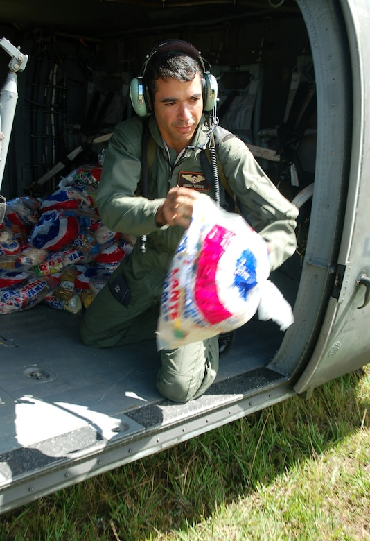 AZUA, Dominican Republic -- 1st Lt. Damian Castro, Dominican air force, tosses bags of food out of an idling UH-60 Black Hawk helicopter to local villagers during a food delivery Nov. 11.  As of Nov. 12, American and British aircrews had delivered more than 241,000 pounds of provisions to the island nation as part of a Combined, Joint, International relief effort following Tropical Storm Noel.  (U.S. Air Force photo by Staff Sgt. Austin M. May)