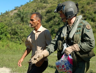 AZUA, Dominican Republic -- Army Specialist Ian Shaffer, a UH-60 crew chief with the 1st Battalion-228th Aviation Regiment deployed from Soto Cano Air Base, Honduras, asks a Dominican man to inform the people of his village safety precautions around an idling Black Hawk during a food delivery Nov. 11.  As of Nov. 12, American and British aircrews had delivered more than 241,000 pounds of provisions to the island nation as part of a Combined, Joint, International relief effort following Tropical Storm Noel.  (U.S. Air Force photo by Staff Sgt. Austin M. May)