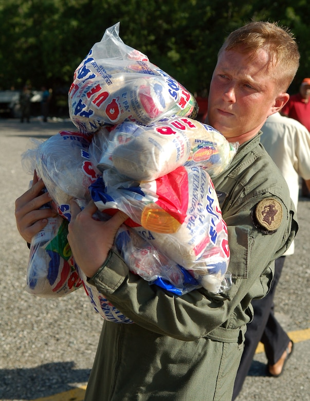AZUA, Dominican Republic -- Army Specialist Ian Shaffer, a UH-60 crew chief with the 1st Battalion-228th Aviation Regiment deployed from Soto Cano Air Base, Honduras, carries a load of food to be delivered to one of three villages in the south-central region of the country Nov. 11.  As of Nov. 12, American and British aircrews had delivered more than 241,000 pounds of provisions to the island nation as part of a Combined, Joint, International relief effort following Tropical Storm Noel.  (U.S. Air Force photo by Staff Sgt. Austin M. May)
