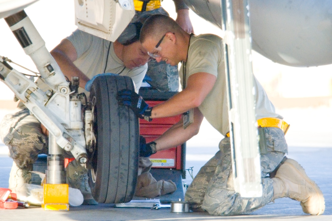 BALAD AIR BASE, Iraq -- Master Sgt. Brian Keeley and Senior Airman Edwin Widgeon, 332nd Expeditionary Aircraft Maintenance Squadron crew chiefs, change the tire on an F-16 Fighting Falcon here, Nov. 10. Sergeant Keeley is deployed from the Colorado Air National Guard's 140th Fighter Wing and Airman Widgeon is deployed from the New Mexico Air National Guard's 150th Fighter Wing. (U.S. Air Force photo/Master Sgt. John Nimmo, Sr.)