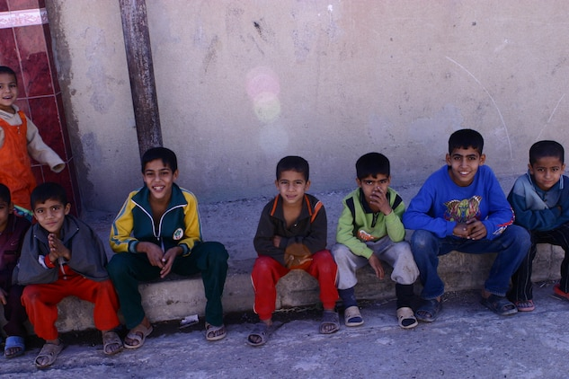 "Children in the Andaloos district of Fallujah sit on the side of the street as they watch Marines pass by on patrol, Nov. 18.  ""If we make a good impression on them, when they grow up, it's going to change this country overall or at least this city,"" said 19-year-old, Phoenix native Pfc. David K. Tietje. Marines with Company K, 3rd Battalion, 5th Marine Regiment, Regimental Combat Team 6, regularly handout school supplies to the children in the district, which encompasses the majority of the city's schools."