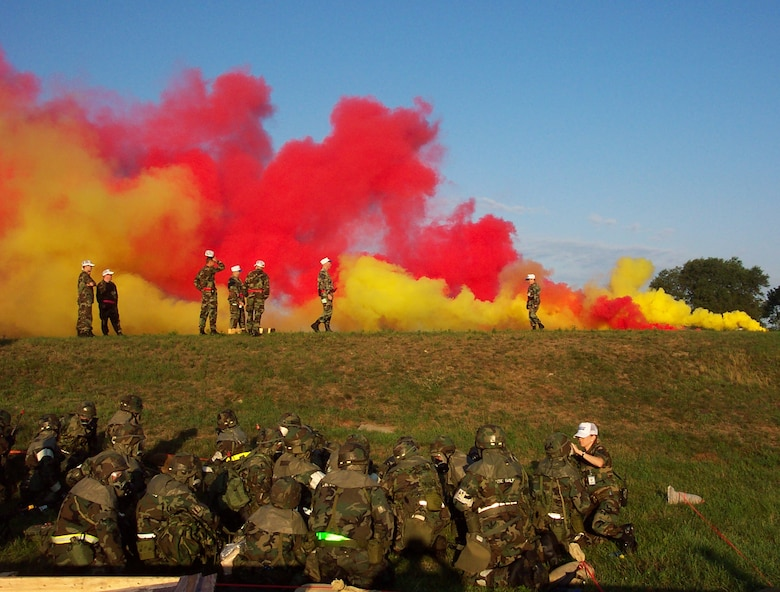 As smoke canisters explode, members of the 85th Aerial Port Squadron take cover at Volk Field, Wisc., during a practice for the unit's upcoming Operational Readiness Inspection. The 85th APS is the 439th Airlift Wing's geographically separated unit located at Hanscom Air Force Base, Mass. (US Air Force photo/Capt. Rebecca Boothby)